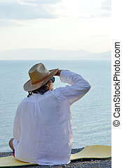 portrait of handsome brunette young man in white shirt cool hat & sun glasses having fun relaxing sitting on the sea or ocean beach & looking into the distance on light blue sky copy space background