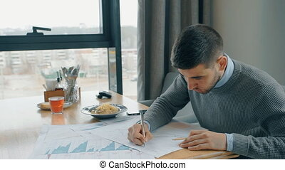 Portrait of handsome businessman correcting financial graphs...