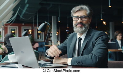 Portrait of handsome businessman looking at camera with serious face in cafe with laptop