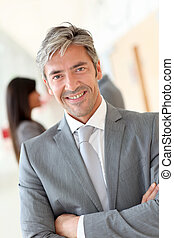 Portrait of handsome businessman standing in hall