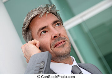 Portrait of handsome businessman talking on mobile phone