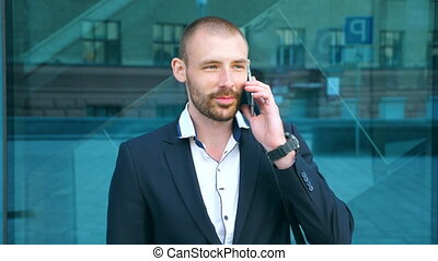 Portrait of handsome businessman talking on phone near office. Young business man speaking on cellphone and having positive emotions. Guy is happy with conversation. Slow motion Close up
