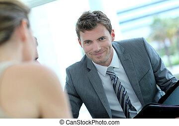Portrait of handsome businessman talking to business partner