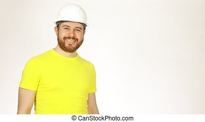 Portrait of handsome cheerful construction engineer or architect in yellow tshirt and hard hat against white background. 4K video