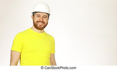 Portrait of handsome cheerful construction engineer or architect in yellow tshirt and hard hat against white background