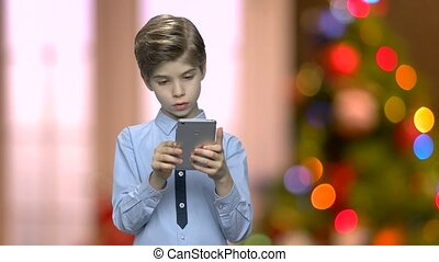 Portrait of handsome child using smartphone.