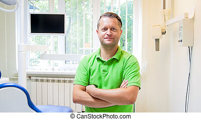 Portrait of handsome confident dentist in dental clinic
