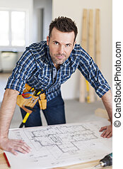 Portrait of handsome construction worker with home plans