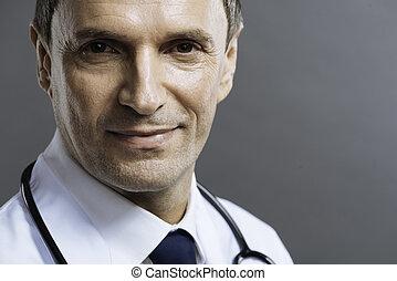 Portrait of handsome doctor smiling on a grey background