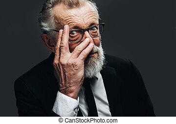 Portrait of handsome elderly CEO posing in black formal suit...