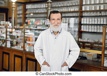 Portrait of handsome elderly male pharmacist, wearing white coat, standing in front of medicines shelves in ancient pharmacy.
