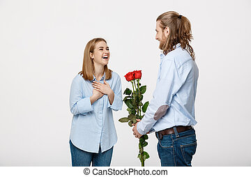 Portrait of handsome elegant guy is surprising his beautiful girlfriend with red roses and smiling over white isolated background.