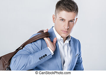 fashion young man in blue suit carrying leather bag -...