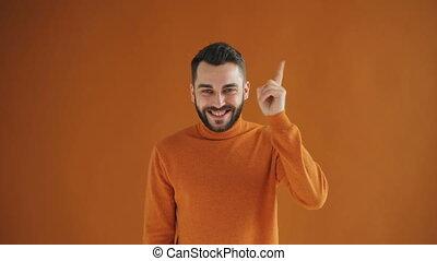Portrait of handsome genius having great idea raising finger...