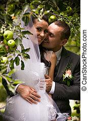 Portrait of handsome groom kissing bride under apple tree