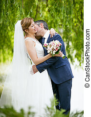 handsome groom passionately kissing bride under tree