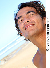 Portrait of handsome guy at the beach