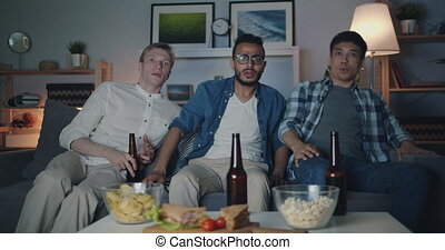Portrait of handsome guys friends watching TV at night with...