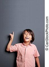 handsome little boy pointing upwards