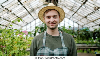 Portrait of handsome man farmer wearing hat and apron...
