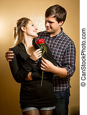 handsome man giving red rose to girlfriend