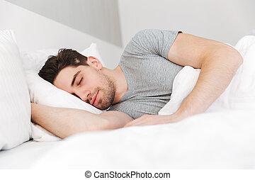 Portrait of handsome man having stubble and wearing casual clothes, sleeping at home in bed with white bedding