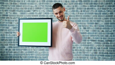 Portrait of handsome man holding chroma key picture frame...
