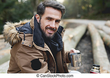 Portrait of handsome man in forest in wintertime