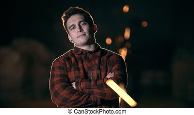 Portrait of handsome man looking at camera among the flying sparks at night