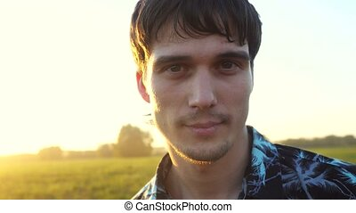 Portrait of handsome man looking at the sun during beautiful sunset with lense flare effects.
