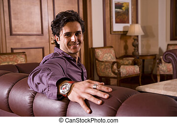 Portrait of handsome man sitting in living room at home