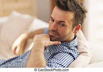 Portrait of handsome man sitting on sofa