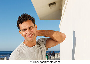 handsome man smiling outside with hand in hair
