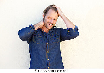 handsome man smiling with hands in hair