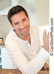 Portrait of handsome man standing in kitchen