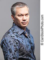 Portrait of handsome man with gray hair in blue shirt
