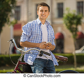 Portrait of handsome man with his bicycle