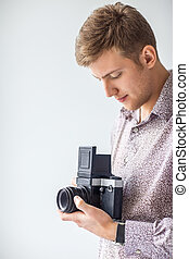 Portrait of handsome man with old medium format camera in ...