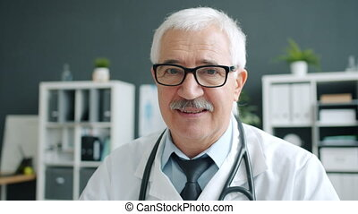 Portrait of handsome senior man doctor smiling at camera indoors in clinic office
