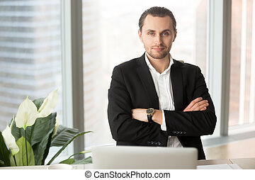 Portrait of handsome smiling businessman in office, looking at c