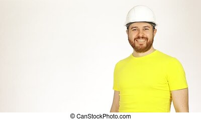Portrait of handsome smiling construction engineer or architect in yellow tshirt and hard hat against white background. 4K shot