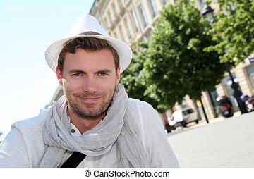 Portrait of handsome trendy man standing in the street