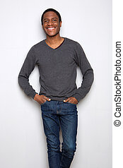 handsome young african american man standing against white background