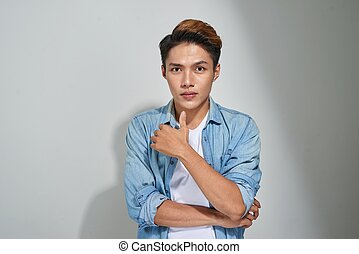 Portrait of handsome young asian guy posing in studio.