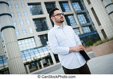 Portrait of handsome young businessman carrying laptop