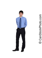 portrait of handsome young businessman standing with hands in his back