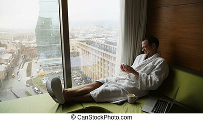 Portrait of handsome young businessman wearing white bath robe sitting on the bed with laptop and cellphone in modern room with sunrise city view on background. Indoors