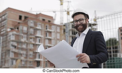 Portrait of handsome young engineer on building site looking at the camera. The builder with construction project stands against the backdrop of a modern building. Slow motion.