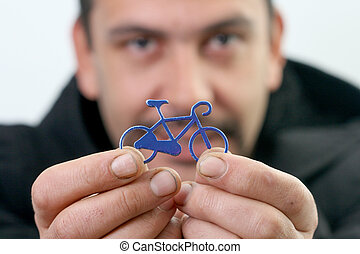 Portrait of handsome young guy with bike toy on a hands