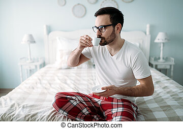 Portrait of handsome young man drinking coffee
